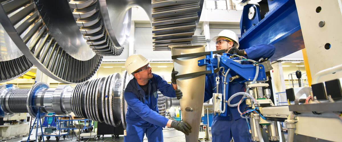 Mechanical engineers assembling a gas turbine for the power industry